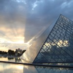 The sun sets over Paris, casting watery reflections of the Louvre's famous pyramid in the pool beneath.
