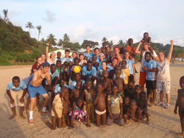 Teen Volunteers and Ghanaian Children Play Soccer on the Beach