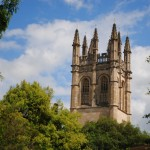 The iconic Magdalen Tower of St. Hilda's college rises above the trees.