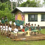In 2013, we also painted a mural at the school and built a playground. Here, the kids are testing out the new see-saw!