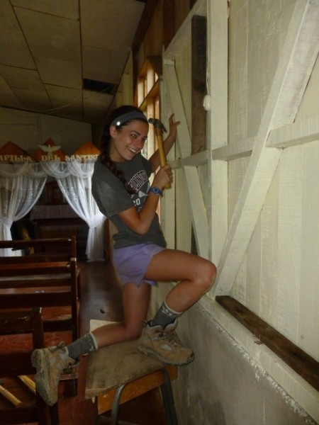 Callie removing nails from the unfinished church walls.